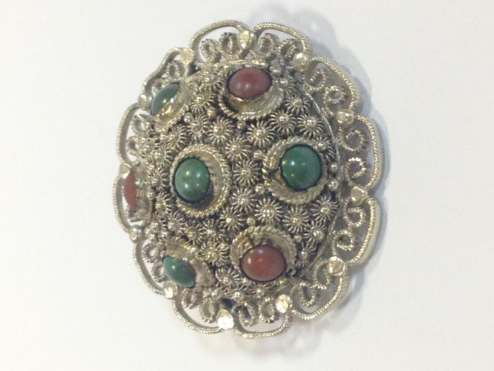 Silver brooch set with natural stones