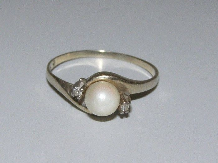 gold ring set with a pearl and diamonds twisted