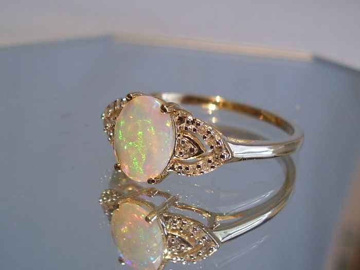 gold ring studded with a opal surrounded by 14
