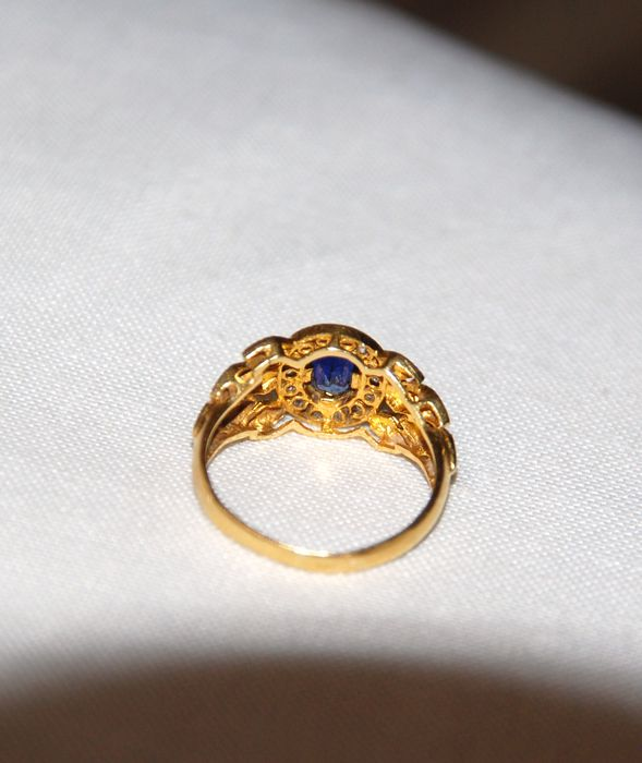 Gold ring with oval cut blue sapphire surrounded by ...