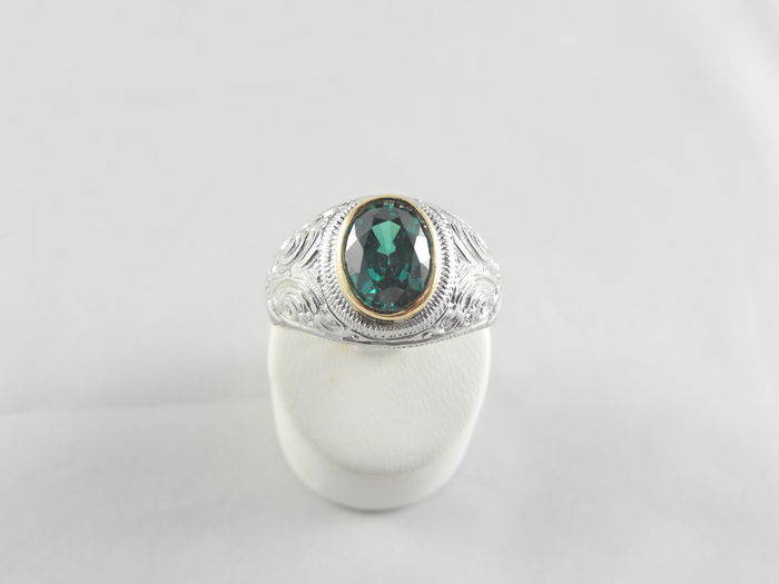 silver ring with a synthetic emerald set in a gold mount