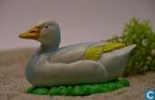 Duck couché blanc / jaune avec de l'herbe