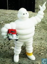 Bibendum, Michelin mascot standing with car