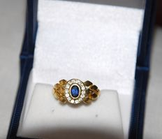 18 kt Gold ring with oval cut blue sapphire and accent diamonds.  Size: 18.47 mm