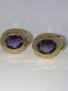 Gold earrings with large facet cut amethyst in smooth surroundings