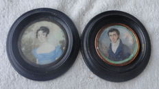 Italian School - Lady in blue dress; Gentleman in blue coat - two portrait miniatures painted on ivory - around 1800