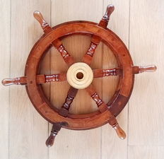 A wooden steering wheel of a boat