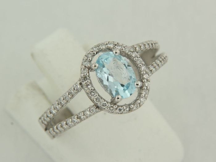 14 kt white gold solitaire ring with central topaz and surrounded and flanked on both sides by 60 diamonds