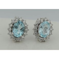 14 kt White gold rosette ear studs set with blue topaz and an entourage of brilliant cut diamonds.