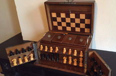 A chess set in a wooden box, with a card game and checker pieces, England, approx. 1920