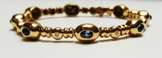 Exclusive solid 18 kt gold bracelet with 9 cabochon cut genuine sapphires and 9 brilliant cut diamonds.
