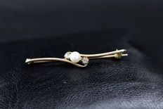Rose gold brooch with diamonds and pearl.