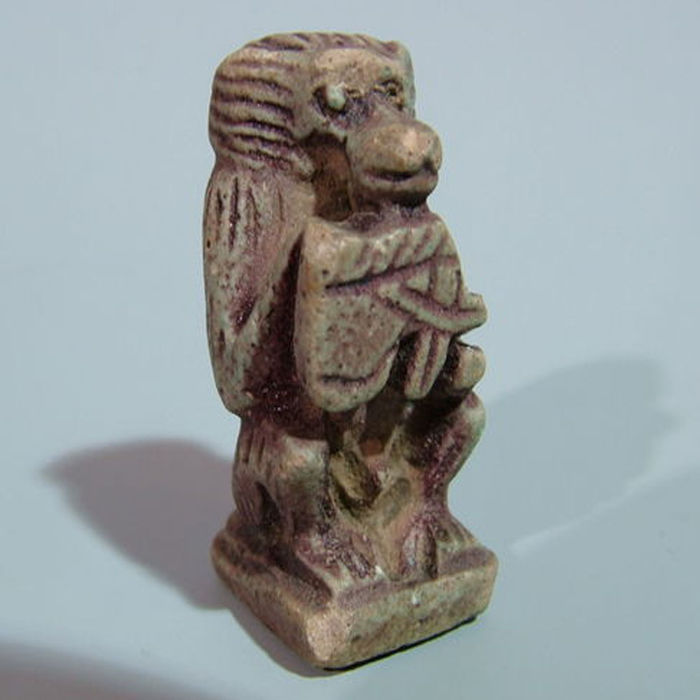 Ancient Egyptian faience amulet of a seated baboon holding a Wedjat-eye - 3 cm