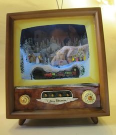 Old TV with scene of snowy landscape and 2 music boxes of matches.