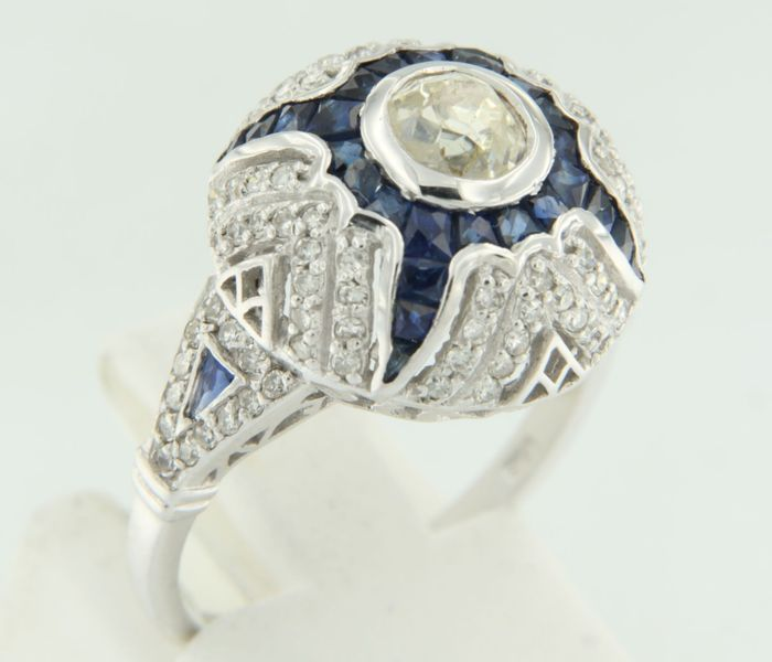 14 kt white gold ring in Art Deco style, set with a central, 0.62 ct old Bolshevik cut diamond, and an entourage of sapphire and single cut diamonds, ring size 17.25 (54).