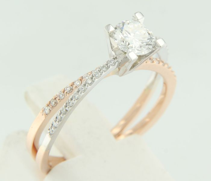 14 kt bicolour gold solitaire ring set with a brilliant cut diamond in the centre and side stones