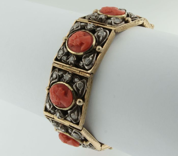 Gold and silver bracelet set with coral, cut in a shape of carved heads, and with rose cut diamonds
