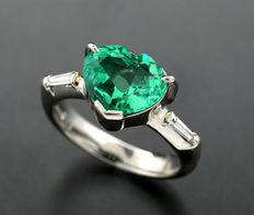 Ring with faceted heart-shaped emerald with extraordinary transparency, 2.35 ct. In 900 platinum, two trapeze cut diamonds, 0.12 ct. H SI.