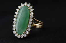 Yellow gold entourage ring with jade and 25 brilliant cut diamonds.