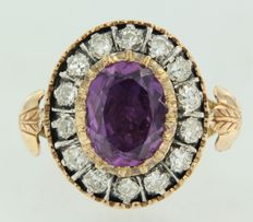 14 kt and Z1 gold with silver entourage ring set with an oval cut amethyst in the centre and octagonal cut entourage diamonds.