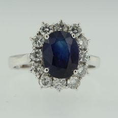 White gold 18 kt entourage ring, set with 4.80 ct oval cut sapphire in the centre and 12 brilliant cut diamonds 1.00 ct, ring size 18 (57)
