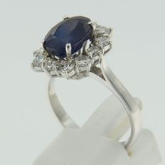 18 kt white gold entourage ring set with a central oval cut sapphire and an entourage of 12 brilliant cut diamonds