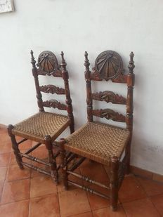 A pair of Spanish Colonial carved and polychrome painted ladder back chairs - probably 18th century