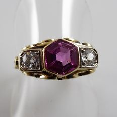 Yellow gold bridge-ring set with two diamonds of 0.20 ct each and a pink, synthetic topaz.