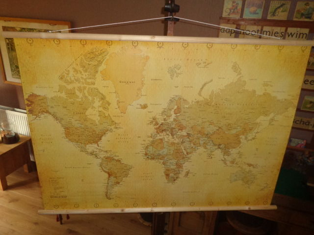 Beautiful as good as new world map in old style (old look) with wooden sticks at top and bottom and hanging cord.