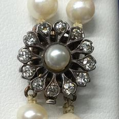 "Two rows, vintage, pearl necklace, ""so called Opera length 75 cm"", with a golden clasp and diamonds. Circa 1960."