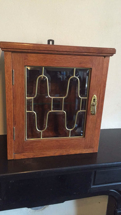 An art deco hanging cabinet with leaded glass door, first half of 20th century