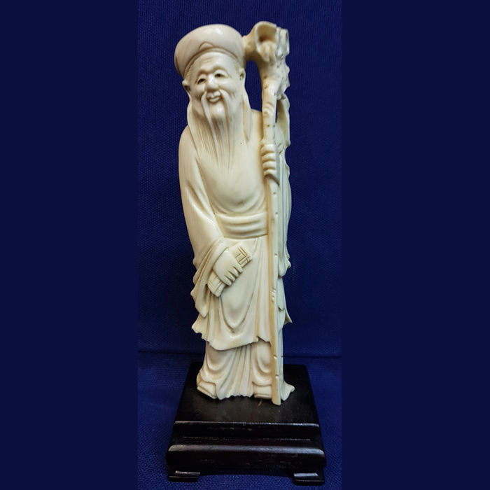 Carved ivory statue depicting an immortal with a stick - China - ca. 1900-1920