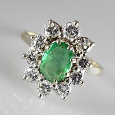 18 kt yellow gold entourage ring with an emerald and 10 brilliant cut diamonds