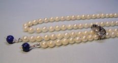 Long, white, Akoya pearl necklace with necklace clip with sapphires
