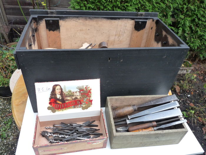 A robust wooden tool box packed with antique tools.