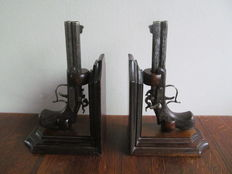 Two bookends decorated with pistols