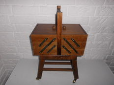 Nice drivable sewing box of wood, with graceful wheels and generously filled with many types of yarn!