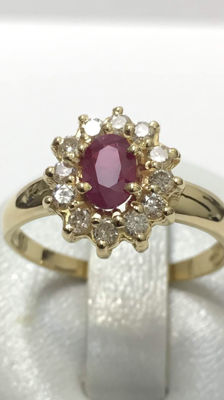 Gold ring set with a lovely ruby surrounded by diamonds.