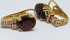Gold earrings, with diamonds and red quartz.