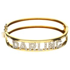 """Yellow gold bangle in 18 kt with white gold letters """"DARLING"""", set with 55 brilliant cut diamonds of approx. 0.55 ct in total - inner size: 62 mm"""