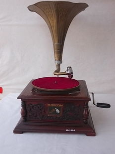 Antique and working gramophone made of chiseled wood with brass trumpet