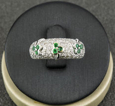 Embossed white gold ring in a raised cloverleaf design, composed of 9 emeralds and 96 diamonds.