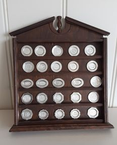 25 sterling silver Franklin Mint miniature plates in a wooden rack.