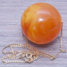 Good-luck charm, composed of a pressed Baltic amber deep orange bead.