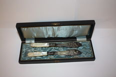 Set of two fish knives with silvered metal blade and mother-of-pearl handle, finely carved, in their ancient original case - Germany, 1900 / 1930