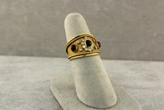 Ring in yellow gold set with diamonds and bezel set with three cabochon rubies