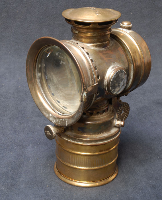 A yellow copper Vitaphare bicycle - carbide lantern.