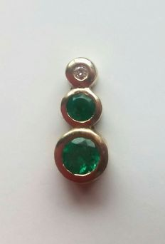 18 kt gold pendant set with emeralds and a diamond.