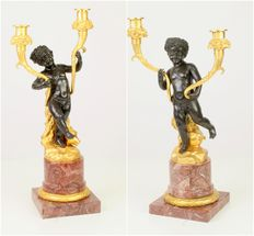 Two bronze candleholders on a marble base after the model of Claude Michel Clodion (1738-1814), recently made