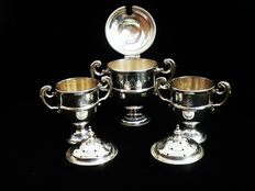 Three piece silver trophy condiment set, mustard pot and salt pepper pots, Horace Woodward & Co Ltd, London, 1898